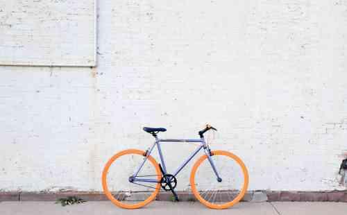 Vélo bleu posé contre un mur