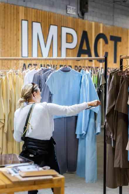 Une femme cherche des vêtements sur un stand IMPACT