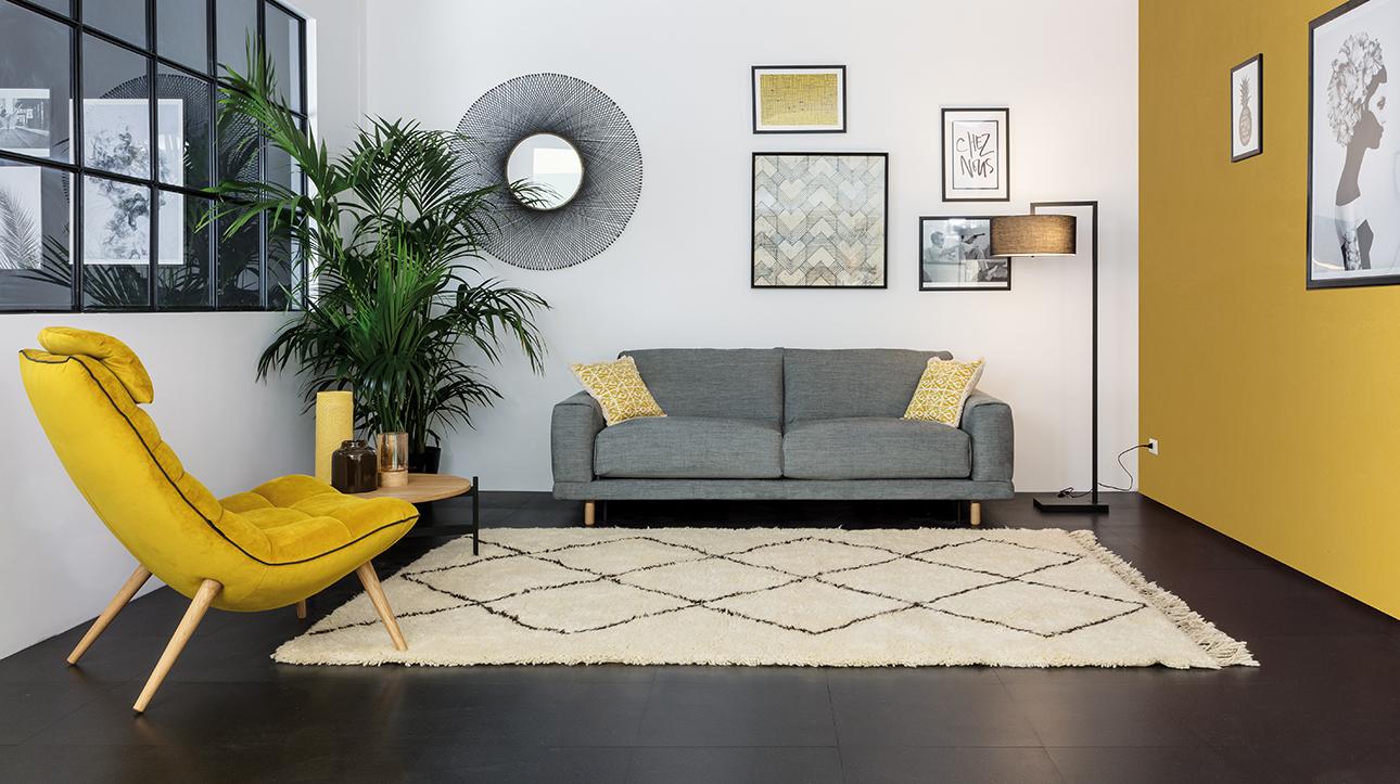 Canapé gris et fauteuil jaune tendances. Aménagement proposé par Convertible Contemporain.