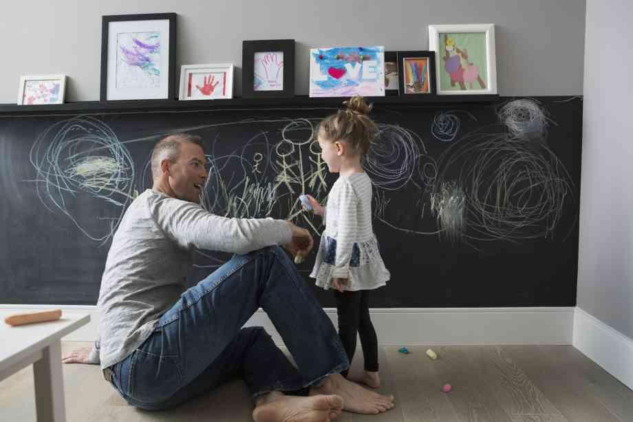 Un père et sa fille devant un tableau noir