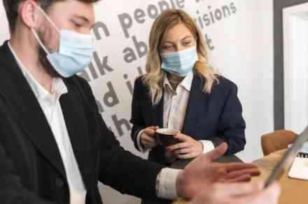 Deux collaborateurs masques sur un stand expoant